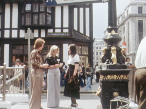 Young women and a man stand outside the Liberty department store in London.