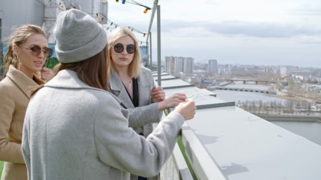 Young women and transgender person smoking on rooftop
