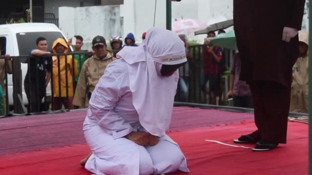 Young women are caned in front of a jeering crowd in Indonesia's Aceh for breaking the province's strict Islamic laws