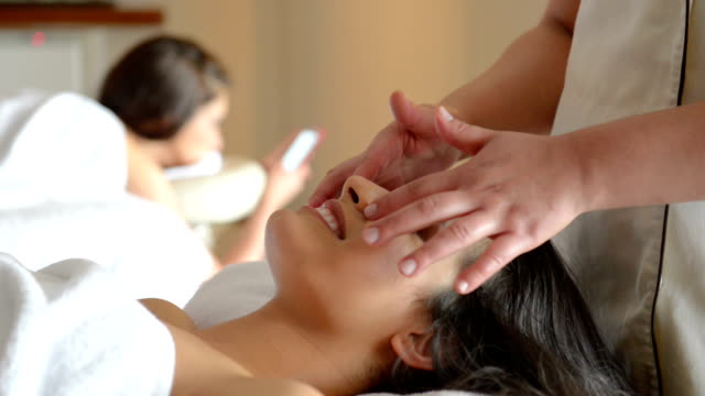 panning: young women at spa treatment - facial massage stock videos and b-roll footage