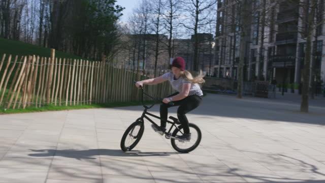 現代の都市環境でサイクリングする若い女性bmxライダー - bmxに乗る点の映像素材/bロール