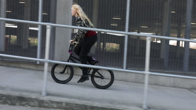 2 young women bmx riders cycling in a modern urban environment - hipster culture stock videos & royalty-free footage