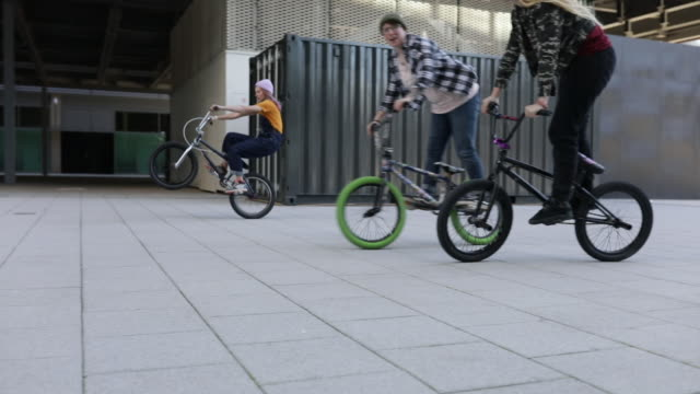 3 young women bmx riders cycling in a modern urban environment - real life stock videos & royalty-free footage