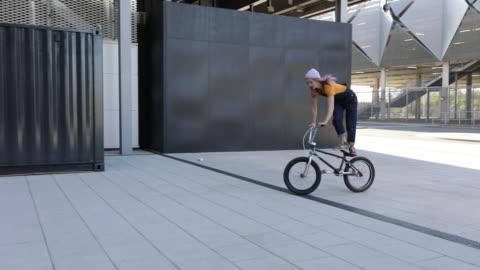 vídeos y material grabado en eventos de stock de 3 mujeres jóvenes bmx ciclistas en bicicleta en un entorno urbano moderno - 18 19 años
