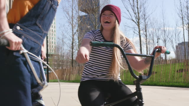 Young women BMX riders fist bump while laughing and joking together