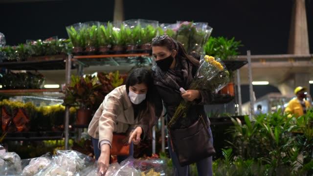 junge frauen kaufen blumen auf demnachtmarkt - mit gesichtsmaske - straßenmarkt stock-videos und b-roll-filmmaterial