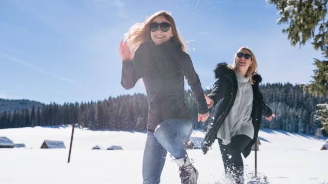 vídeos de stock, filmes e b-roll de mulheres jovens, perseguindo uns aos outros na paisagem de inverno - brincadeira de pegar