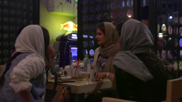 young women chat and drink coffee at a raees coffee store in tehran, iran, on friday, aug 21, 2015 shots: illuminated signage outside the cafe - coffee drink stock videos & royalty-free footage