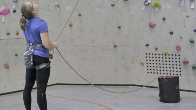young women climbing on indoor climbing wall - climbing rope stock videos & royalty-free footage