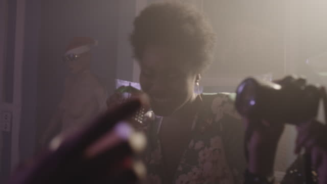 stockvideo's en b-roll-footage met young women dancing at party with camera - cocktail