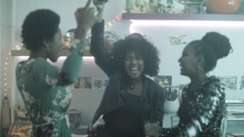 vidéos et rushes de young women dancing together at party in kitchen - trois personnes