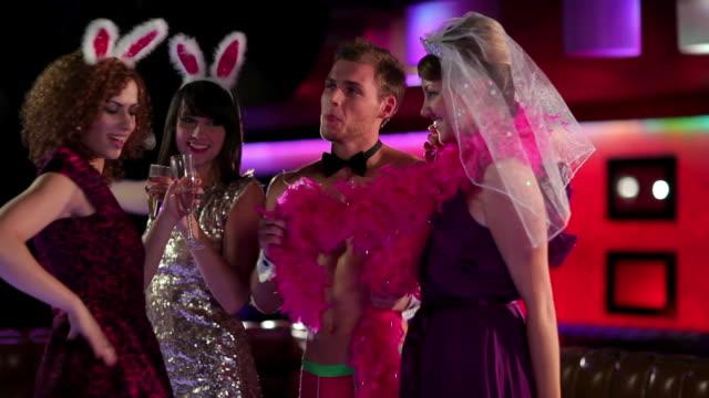 vídeos de stock, filmes e b-roll de young women dancing with male stripper on hen night - sc47