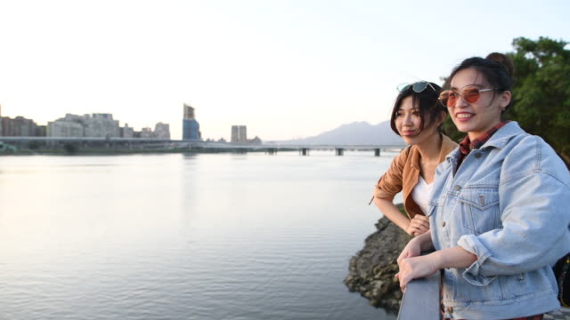 young women discovering taipei enjoying the sunset down by the river - seeing paris: on the boulevards stock videos & royalty-free footage