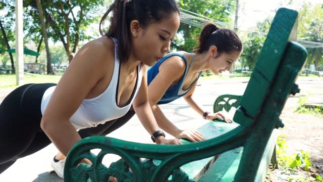 Young women doing pushups together outdoor at the park