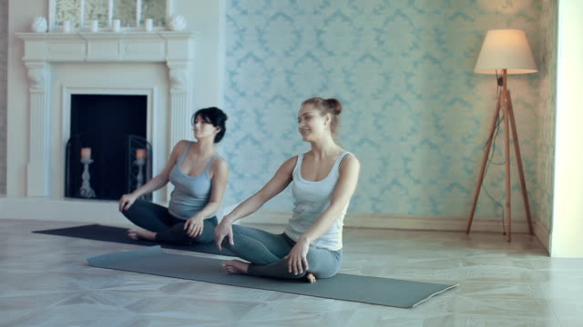 young women doing yoga meditation and stretching exercises - lotus position stock videos and b-roll footage