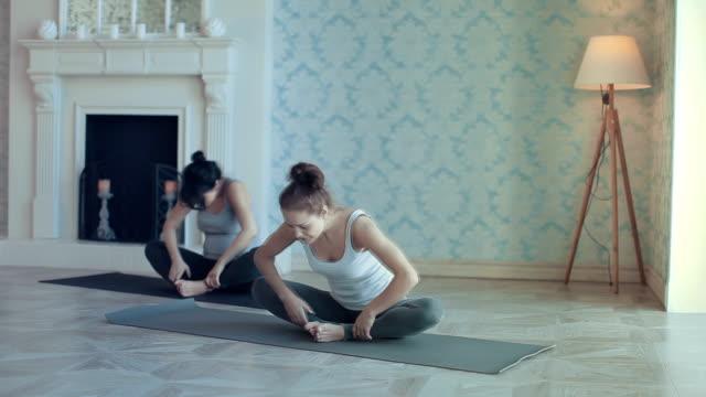 vídeos de stock, filmes e b-roll de jovens mulheres fazendo yoga meditação e exercícios de alongamento - tatame equipamento para exercícios