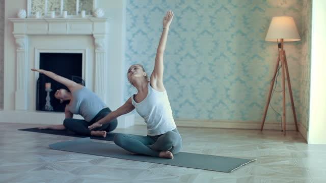 vídeos y material grabado en eventos de stock de jóvenes haciendo yoga meditación y ejercicios de estiramiento - centro de yoga