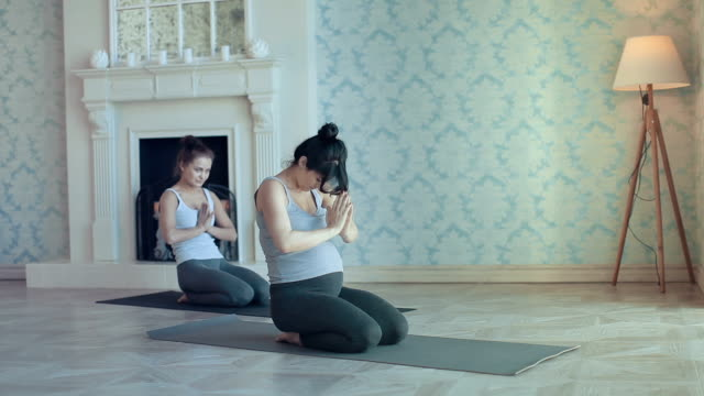 young women doing yoga meditation and stretching exercises - pilates stock videos and b-roll footage