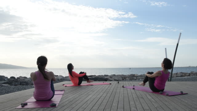 young women doing yoga on the beach - viewpoint stock videos & royalty-free footage