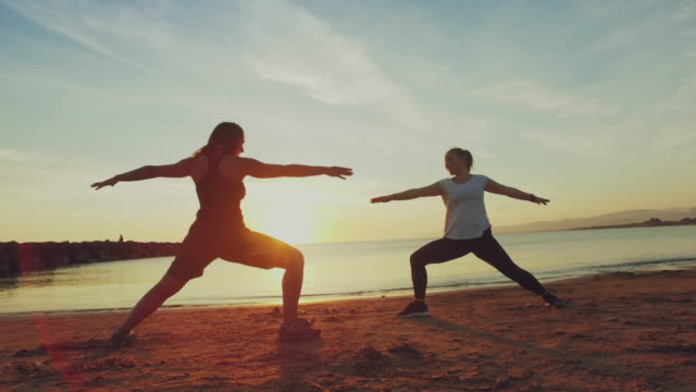 young women doing yoga on the each at sunset - sun salutation stock videos & royalty-free footage