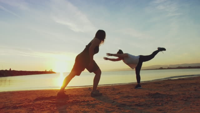 young women doing yoga on the each at sunset - sun salutation stock videos and b-roll footage