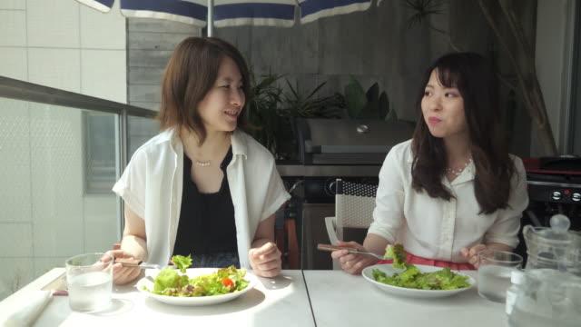 カフェのバルコニーでサラダを食べる若い女性 - 向かい合わせ点の映像素材/bロール