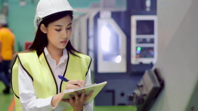young women engineer inspecting with tablet computer the work process of industrial cnc metal machining.technology,industry,science,innovation,education,industry 4.0,women in stem.automation – large scale industrial concept.blue collar workers - production line stock videos & royalty-free footage