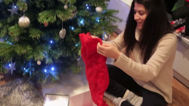 Giovane donna godendo il regalo ricevuto per Natale.