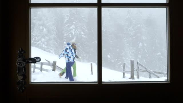young women enjoying winter, view through window - skijacke stock-videos und b-roll-filmmaterial