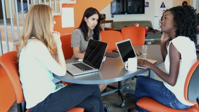 vidéos et rushes de jeunes femmes entrepreneurs dans une réunion d'affaires - hot desking