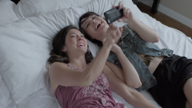 young women fall back onto hotel bed and laugh at photos on smartphone - ホテル点の映像素材/bロール