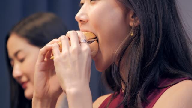 若い女性の友人が楽しんで一緒においしいハンバーガーやドリンク自宅の夜の灯の中に座っています。ライフ スタイル: マイルス トーン ・お祝い - unhealthy eating点の映像素材/bロール