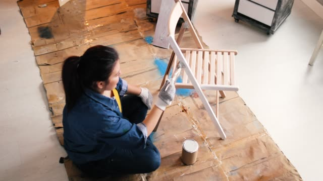 vídeos de stock e filmes b-roll de young women furniture designer painting chair in garage - bricolage