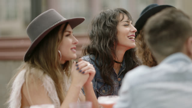 young women gesture and laugh with diverse group of friends over drinks at happy hour on outdoor bar patio. - generazione y video stock e b–roll
