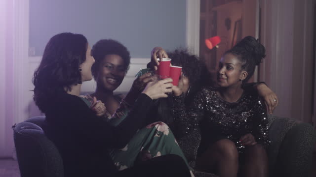 Young women having drinks in sofa at party