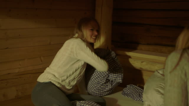 Young women having pillow fight on bunkbed