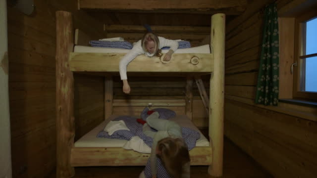 vidéos et rushes de young women having pillow fight on bunkbed - chalet