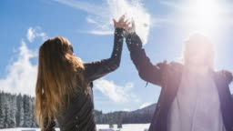 Young women high fiving in winter landscape