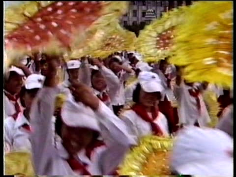 young women holding paper sunflowers participate in compulsory synchronised celebration parade in kim il sung square pyongyang aug 88 - parade stock videos & royalty-free footage