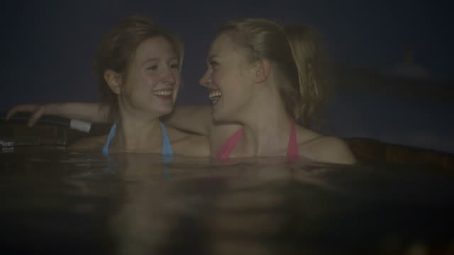 stockvideo's en b-roll-footage met young women in bikini enjoying steam water in hot tub during winter - sauna