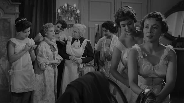 young women in dressing room changing and talking when old house keeper enters the room to tell a girl someone is looking for her. dramatization. - collaboratore domestico video stock e b–roll