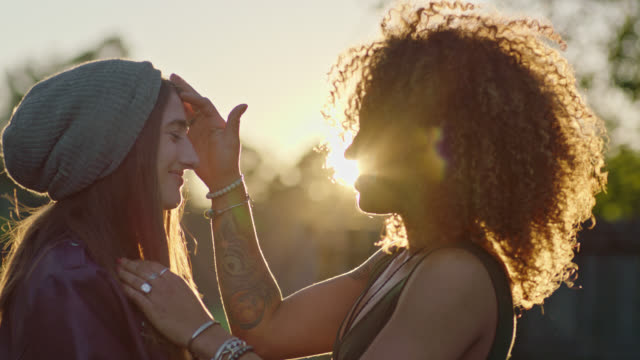 stockvideo's en b-roll-footage met young women in love share a kiss and embrace as the sun sets. - romance
