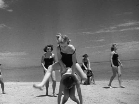 b/w 1951 young women in swim suits playing leap frog on beach / st. petersburg, fl - leapfrog stock videos & royalty-free footage