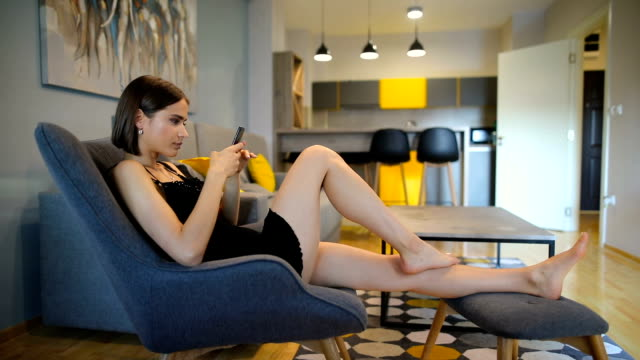 young women in the chair using smart phone in morning. girl in love in chair checking social apps with smartphone. smiling woman surfing net with cellphone at home. mobile addict concept - armchair stock videos & royalty-free footage