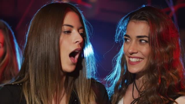 vídeos y material grabado en eventos de stock de las mujeres jóvenes en la noche club 4k - coquetear