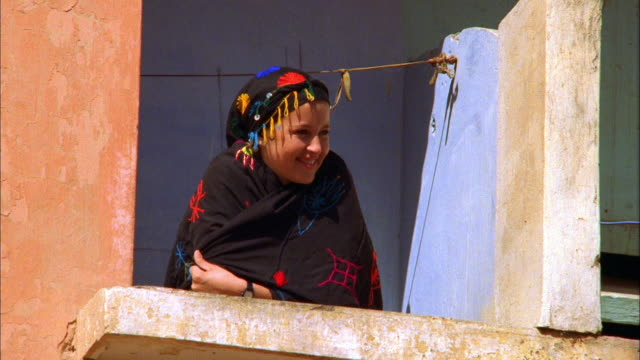A young women in traditional dress smiles as she leans over the ledge of a balcony. Available in HD.