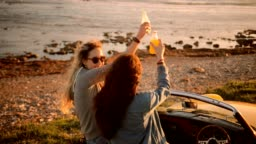 Young women in vintage convertible car drinking soda at beach