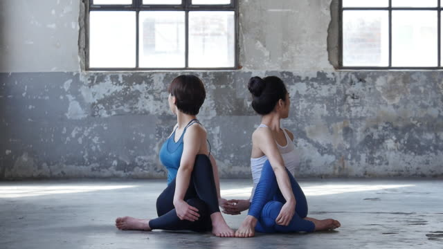 vídeos de stock, filmes e b-roll de young women in yoga outfit sitting and doing yoga pose indoors - sem manga