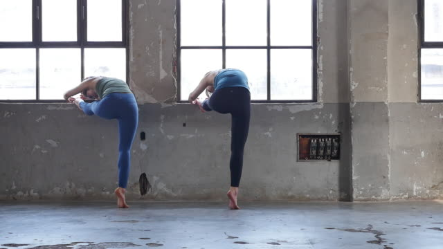 young women in yoga outfit standing and stretching indoors - ärmelloses oberteil stock-videos und b-roll-filmmaterial