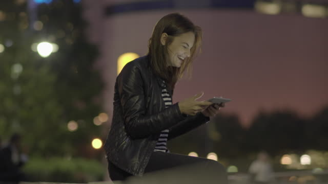 young women laughing during video chatt conversation outdoors at night - hose stock-videos und b-roll-filmmaterial